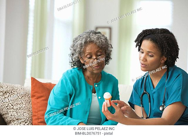 African home nurse reviewing prescription bottle with patient
