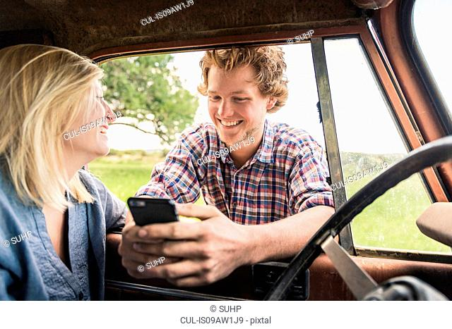 Young man with girlfriend reading smartphone texts at jeep window