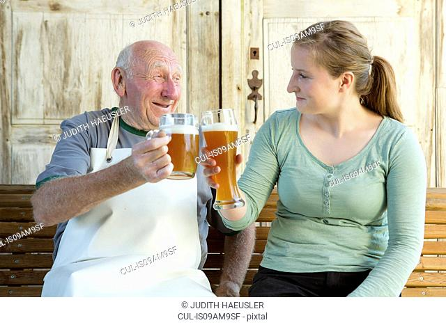 Senior man and young woman toasting with beer