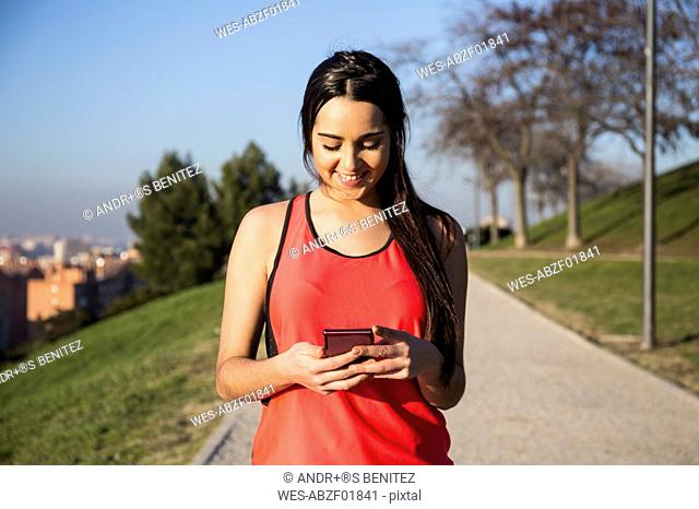 Smiling female athlete using her phone
