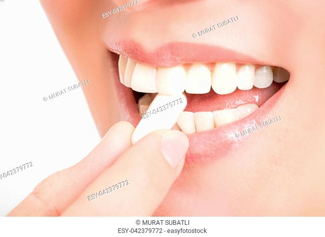 Film tablet between the teeth of a woman