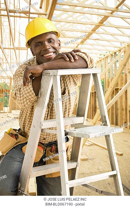 African construction worker in hard-hat sitting on ladder
