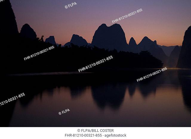 View of limestone karst formations along river at sunrise, Yellow Cloth Shoal, Li River, Guilin, Guangxi Zhuang Autonomous Region, China, October