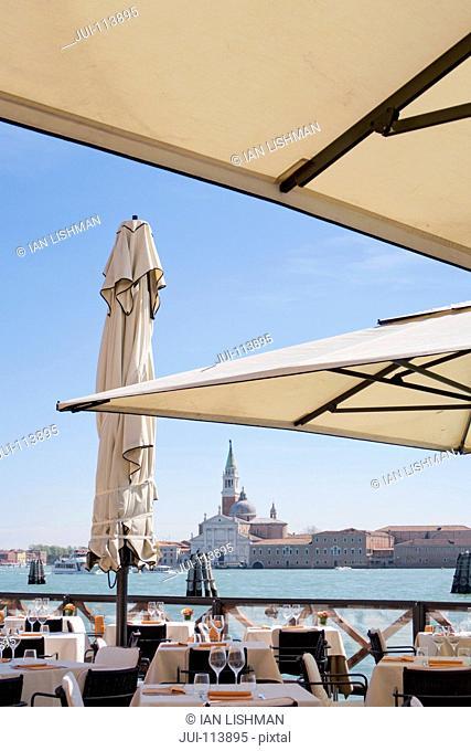 View of San Giorgio Maggiore architecture beyond sunny Grand Canal patio restaurant in Venice, Italy