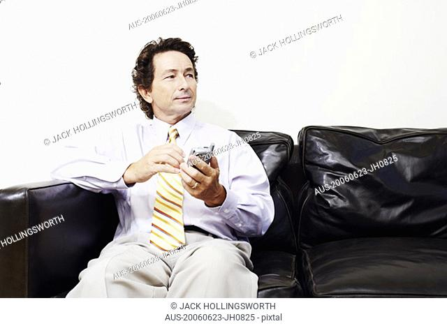 Businessman sitting on a couch and holding a mobile phone