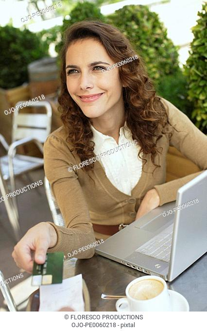 Woman on outdoor patio handing credit card to waiter
