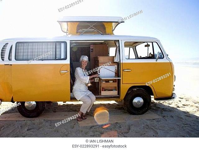 Senior woman making tea in camper van on beach, smiling, portrait (lens flare)
