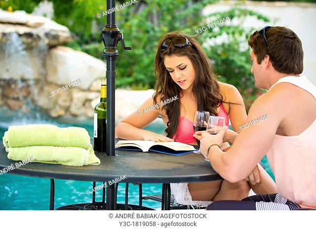 Young couple sitting at a table in a vacation resort's swimming pool area reading and enjoying wine