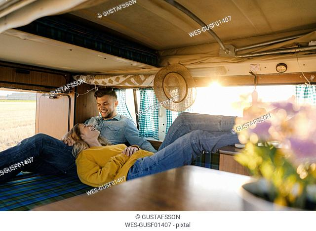 Happy young couple relaxing inside camper van