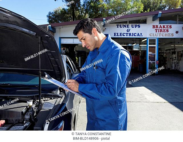Middle Eastern mechanic writing on clipboard