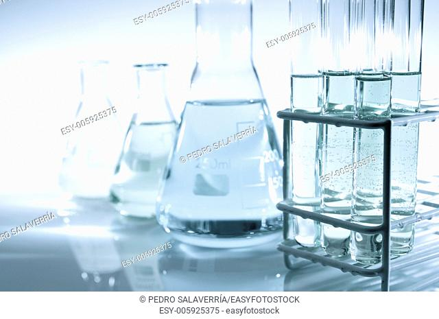 test tubes and flasks with green and blue liquid in a laboratory