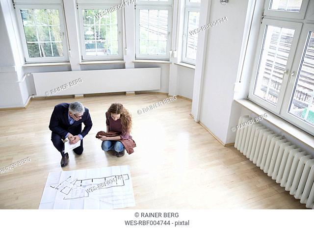 Real estate agent showing construction plan to client in empty apartment