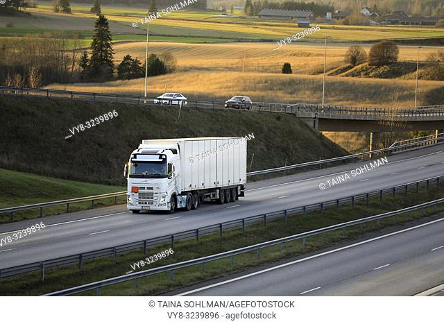 Salo, Finland - November 18, 2018: White Volvo FH semi trailer driving among motorway traffic at sunset time in late autumn