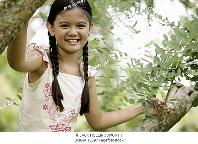 Young girl sitting in tree, smiling at camera