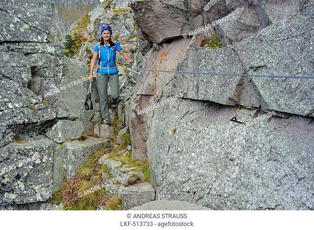Woman hiking on fixed rope route between boulders, Trans-Lagorai, Lagorai range, Dolomites, UNESCO World Heritage Site Dolomites, Trentino, Italy
