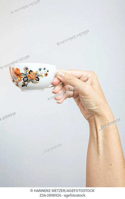 Hand holding a vintage tea cup with flowers
