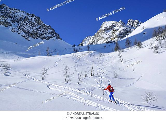 Woman back-country skiing ascending to Passo Croce, Rocca Peroni in the background, Passo Croce, Valle Maira, Cottian Alps, Piedmont, Italy