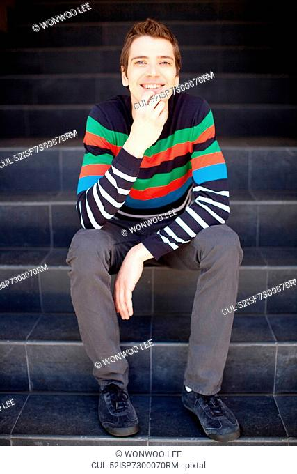Man in colorful sweater on staircase