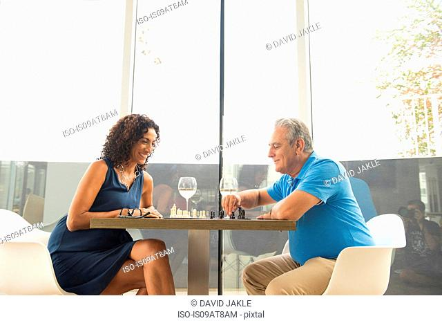 Senior man and wife playing chess and drinking wine