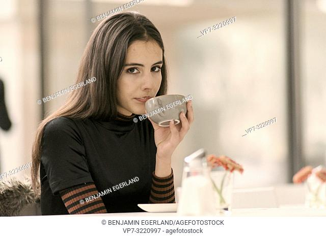 portrait of calm relaxed woman sipping coffee while enjoying break at table in café, in Munich, Germany