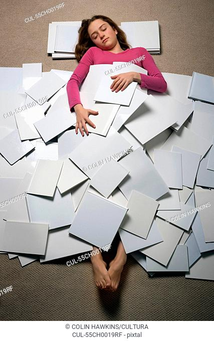 Girl lying on floor asleep covered with pieces of paper