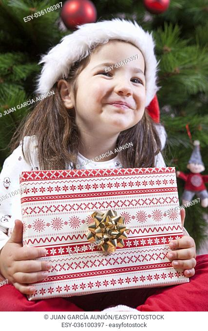 Little girl opening her present under Christmas tree. She is very, very happy