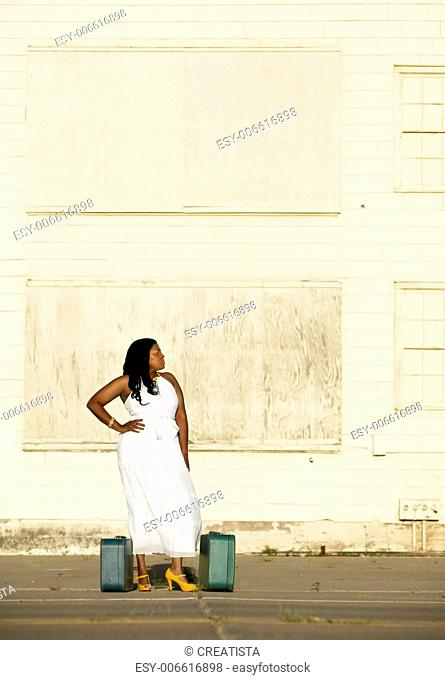 African American woman with suitcases waits outside an industrial building