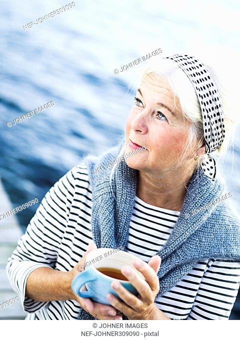 A senior woman drinking tea on a jetty