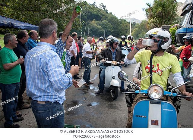A man pouring cider for participants in the concentration of scooters. Llanes, Asturias