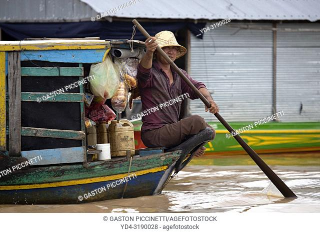 Man on the boat selling food, Chang Kneas floating village, Siem Reap Province, Cambodia. Chang Kneas, is one of the more than 170 villages surrounding the...