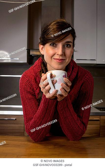 Smiling Woman Holding Cup with Pink Hearts in Kitchen