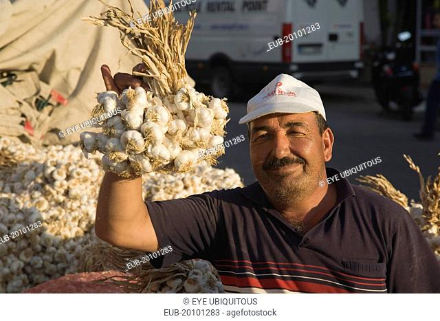 Stallholder at weekly market holding up bunch of garlic bulbs with more garlic piled up and in sacks behind. Late afternoon summer sunshine