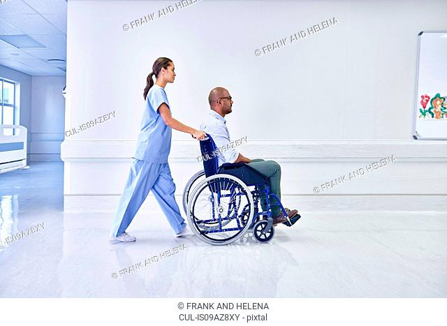 Doctor in hospital pushing patient in wheelchair