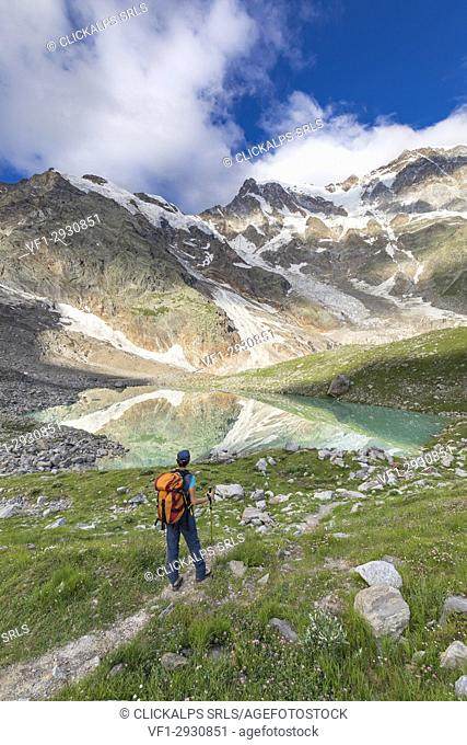 A girls looks the Locce Lake and the East face of Monte Rosa Massif (Locce Lake, Macugnaga, Anzasca Valley, Verbano Cusio Ossola province, Piedmont, Italy