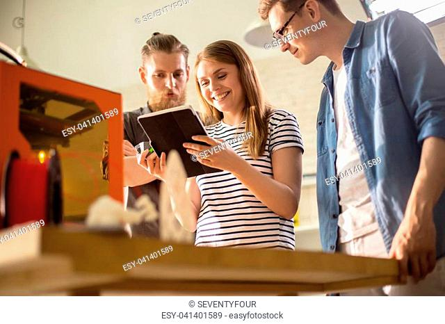 Portrait shot of attractive young designer showing work results to her male colleagues with help of digital tablet while working together on ambitions project
