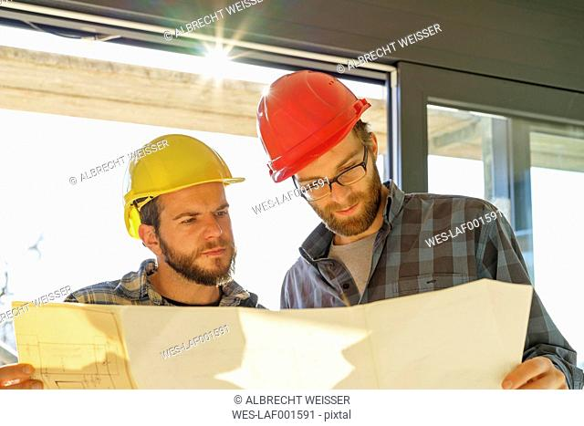 Two craftsmen looking at building plan in construction site