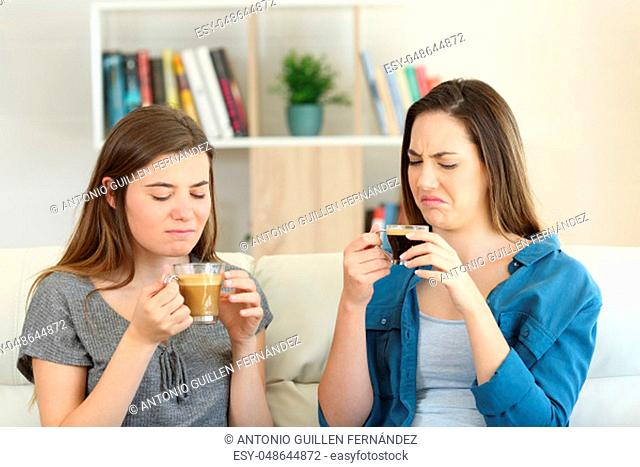 Two friends drinking coffee with bad flavour sititng on a couch in the living room at home