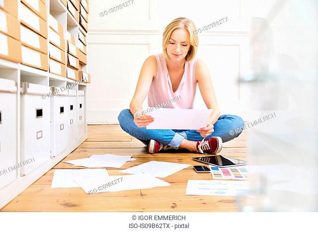 Female designer sitting on floor creating mood board in creative studio