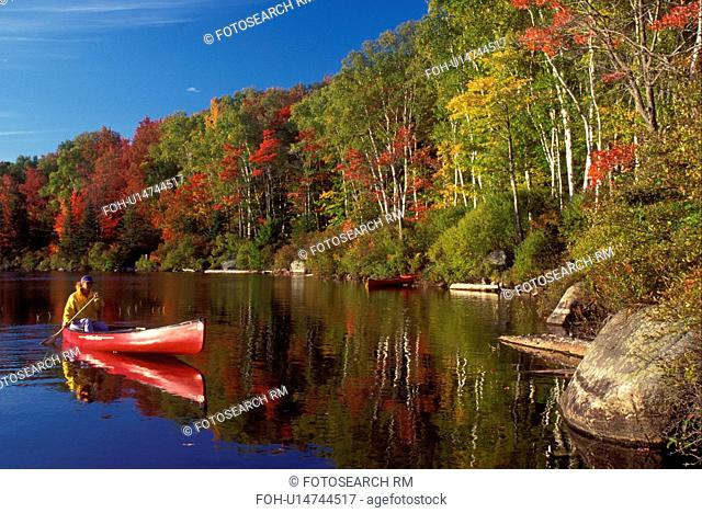 Vermont, canoe, canoeing, Woman paddling a red canoe on a sunny fall day on Kettle Pond in Groton State Forest. Mad River Canoe Products