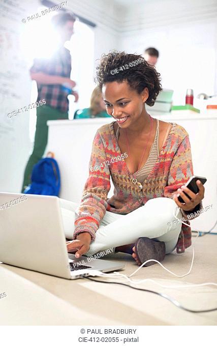 Businesswoman using laptop on floor in office