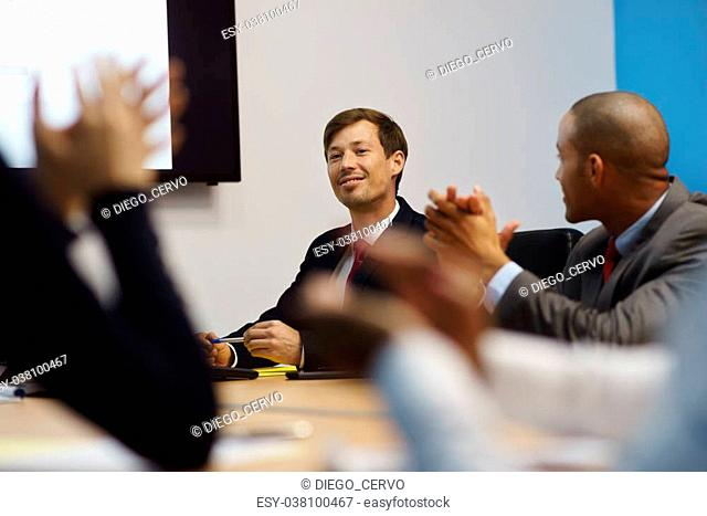 Group of business people meeting in corporate conference room, applauding at a coworker during his presentation. The man is showing charts and slides on a big...