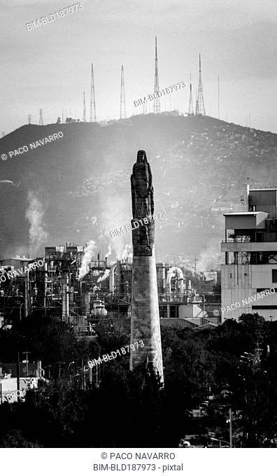 Statue on pillar in cityscape