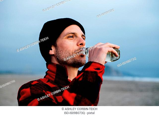 Man drinking bottled water on beach, Morro Bay, California, USA