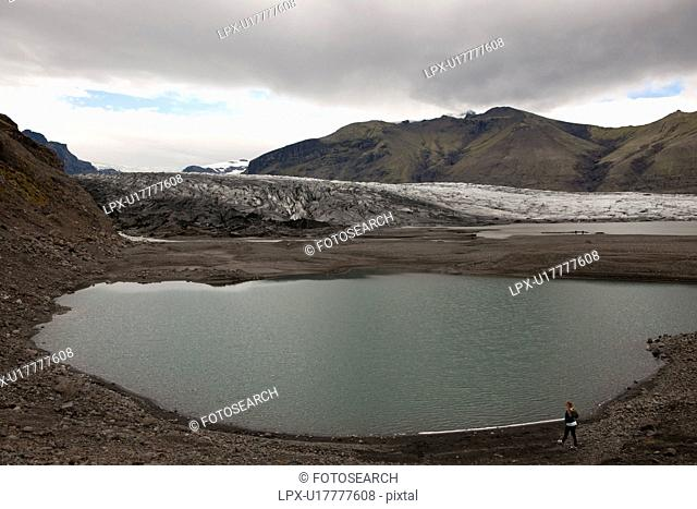 Glacier and glacial lake surrounded by mountains on cloudy day