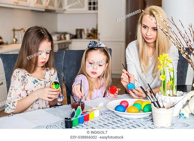 Young mother and her two daughters painting Easter eggs. Cozy home atmosphere. Easter