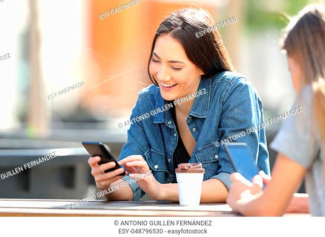 Happy women using their smart phones sitting in a table in a park
