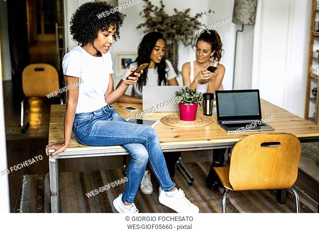 Woman with cell phone sitting on table with friends in background