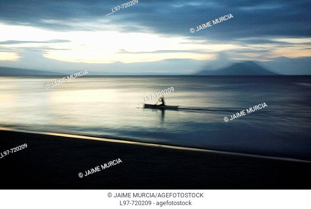 Tavurvur Volcano in the distance, a fisherman rows offshore near the town of Kokopo which has since become the main town for East New Britain since the eruption...
