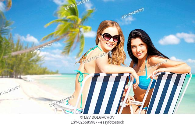 summer holidays, people, leisure, vacation and travel concept - happy women sunbathing in chairs over exotic tropical beach with palm trees and sea shore...