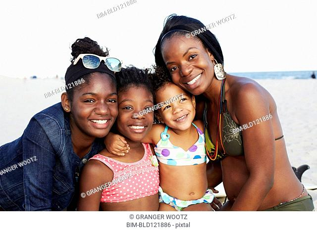 Mother and daughters smiling on beach